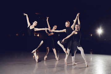 A group of ballerinas are dancing on the scene against a black background.