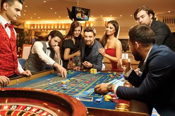 Happy people gambling poker roulette in casino Wall mural