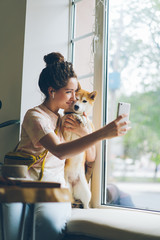 Cute woman taking selfie with shiba inu dog sitting on window sill in cafe using smartphone camera holding device posing smiling. People and animals concept.