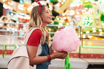 Tuinposter Amusementspark Image of blonde charming woman eating sweet cotton candy while walking in amusement park