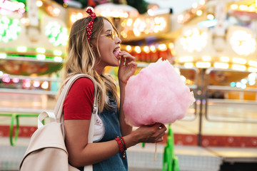 Image of pretty cute woman eating sweet cotton candy while walking in amusement park