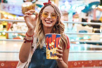 Image of young blonde woman smiling and holding popcorn while walking in amusement park