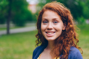 Close-up portrait of beautiful young lady with long red hair and freckles smiling looking at camera in park in summer. Nature, people and happiness concept.