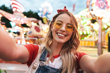 Wall Murals Amusement Park Image of young blonde woman laughing and taking selfie photo at amusement park