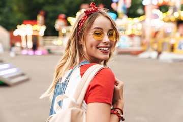 Image of pleased blonde woman smiling and walking in front of colorful carousel at amusement park