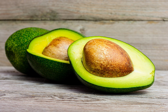 Halved green avocado with stone on wooden background. A juicy green avocado on a wooden kitchen table. Healthy tropical fruits.