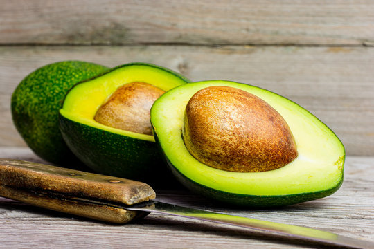 Whole, quartered and halved green avocado on wooden background. A juicy green avocado on a wooden kitchen table. Healthy tropical fruits.