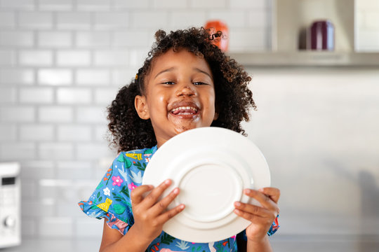 Laughing little girl licking chocolate off plate