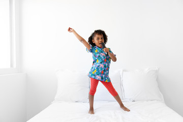 Young girl singing with hairbrush as a microphone dancing on bed