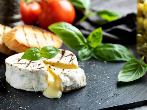 Camembert cheese grill ,on black stone background