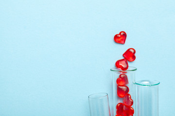 Hearts and test tube. Baby from tube vitro glass. Artificial insemination, IVF. Blue background. Copy space for text.