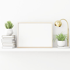 Interior poster mockup with horizontal gold metal frame standing on the table with plants in pots, lamp and pile of books on empty white wall background. 3D rendering, illustration.