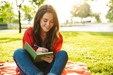 Image closeup of smiling girl student listening music with headphones while sitting in green park