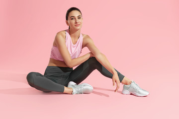 Fitness woman model in fashion sportswear on pink background