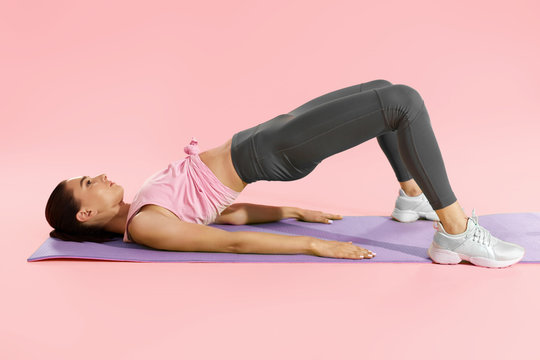 Fitness woman doing hip workout exercise on yoga mat at studio