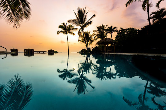 Clear Blue Infinity Pool of a Vacation Destination with Reflection in Water of Perfect Tropical Island Paradise of Palm Trees Silhouettes and Awesome Colorful Sunset Sky Over Ocean in Hawaii