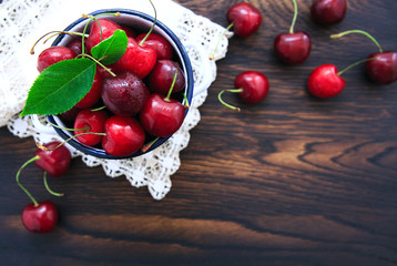 Cherries on brown wooden table with water drops.