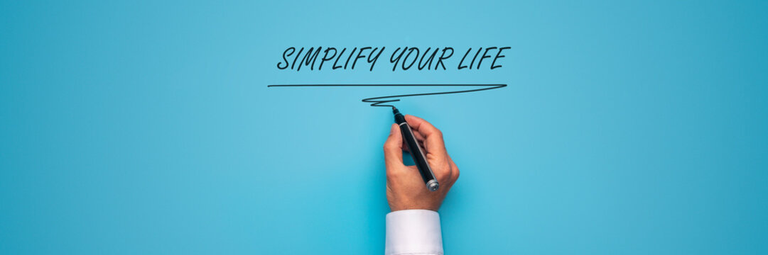 Male hand writing a Simplify your life sign with black marker over
