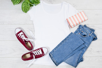 Fototapeta White female t shirt mock up flat lay on wooden background. Top front view t-shirt and copy space. Mockup t-shirt and summertime. Template blank shirt. obraz