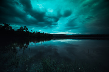 moonlight shines behind a cloudy at night over tranquil lake Wall mural
