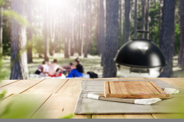 Table top background and sunny forest and garden view in distance. Empty space on the table top for an advertising product.