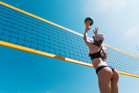 girls playing beach volleyball. Beach volleyball championship. The woman reaches for the ball. throwing a yellow volleyball over the net. Victory point. Outdoor sports games.