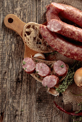 Fototapete - Dry-cured sausage with bread and spices on a old wooden table.