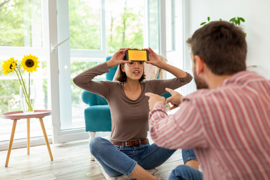 Couple playing charades wtih a smartphone app