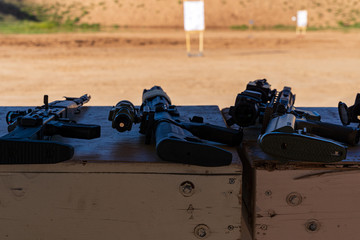 Semi-Automatic Rifles laying on bench at outdoor firearms shooting range
