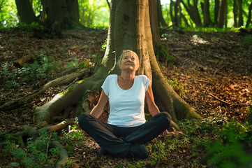 Experience the forest while bathing in the forest (Shinrin Yoku) with all her senses. A 50 year old blonde woman sits cross legged relaxed. She feels the sun and the atmosphere