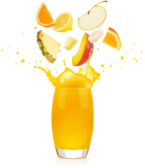 Wall Mural - pieces of fruit falling into a yellow juice glass splashing on white background