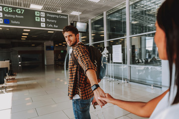 Wall Mural - Serious guy is leading girlfriend to plane