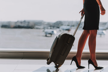 Wall Mural - Elegant woman is going to fly with suitcase