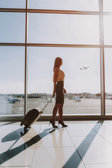 Wall Mural - Elegant female is looking at plane from airport