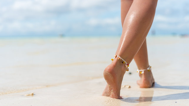 Beach travel concept. Sexy Legs on Tropical Sand Beach. Walking Female Feet. Closeup