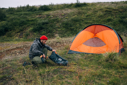 Young male explorer tourist unpacks his dry bag or backpack with camping gear, sleeping matress and hiking food, sets up camp next to tent in wild national park forest or field. Adventure lifestyle