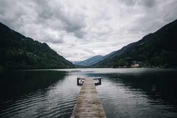 Landscape shot of pristine clean alpine lake in mountain forest on cloudy and rainy day, untouched clear water reflects clouds. Wooden pier reaches out, perfect location for meditation and yoga