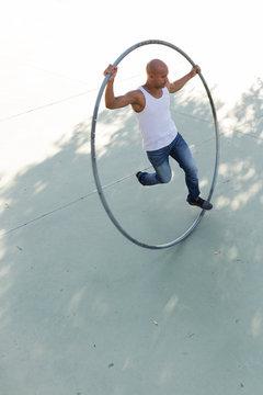 Cyr wheel acrobat training tricks in a park in sunny day