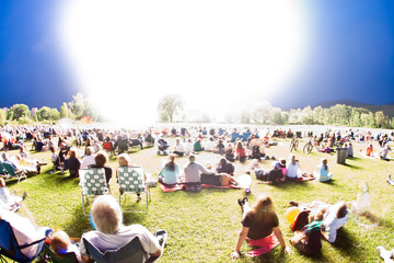 Digitally manipulated image of bright light and a field of people.