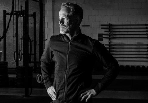 Älterer sportlicher Mann in den Fünfzigern im Fitnesscenter. Der attraktive grauhaarige Athlet mit Bart trägt eine schwarze Jacke und schaut in die Ferne. Schwarz und weiß.