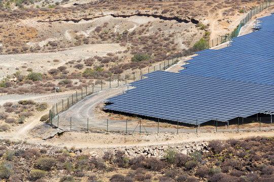 Blue solar panels at photovoltaics power station farm, future innovation energy concept, clear blue sky background, Granadilla, Tenerife
