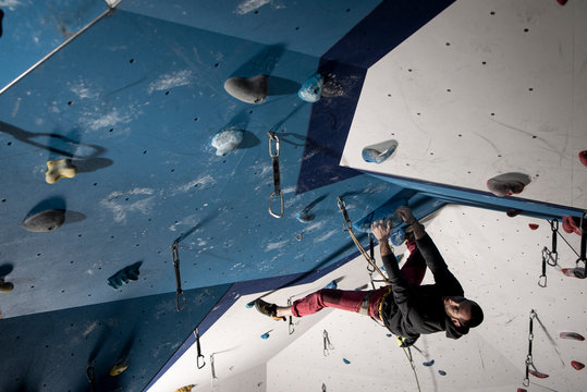 Man sending a difficult route of sport climbing in climbing gym.