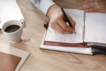 Man writing in daily planner with black pen