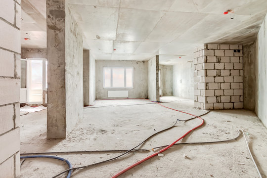 Built structure construction site of residential apartment building. Interior in progress to new house with windows and white brick wall with electric colored wires on the floor.