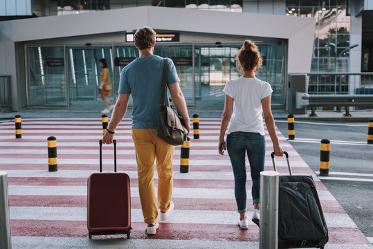 Young man and woman with travel suitcases crossing the road in airport