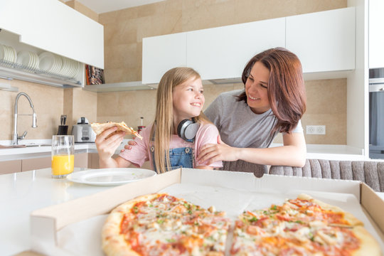Mother and daughter sitting in the kitchen, eating pizza and having fun. Focus on daughter