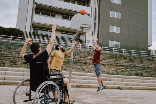 a man in wheelchair plays basket with friends