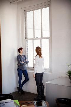 Two young women talking near window
