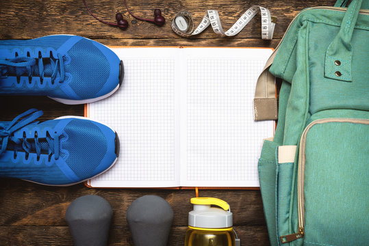 Blank fitness gym exercise list with blank pages, sneakers and bag on a wooden floor background.