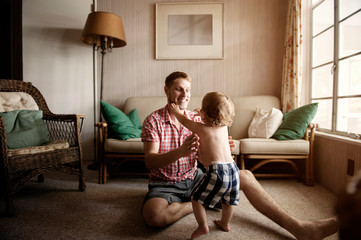 Smiling father playing with his son at home